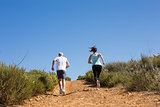 Fit couple jogging up mountain trail