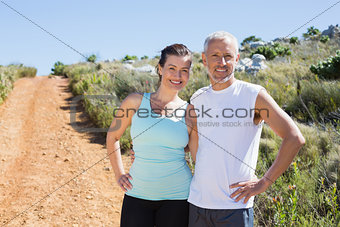 Fit smiling couple embracing and smiling at camera on country trail