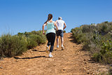 Fit couple running up mountain trail