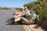 Hiking couple sitting on the side of the road smiling at camera