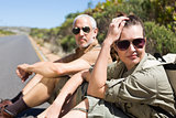 Hiking couple sitting on the side of the road looking at camera