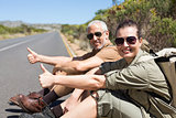 Hitch hiking couple sitting on the side of the road smiling at camera