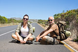 Hitch hiking couple sitting on the side of the road looking at camera