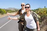 Hitch hiking couple standing on the side of the road with thumb out