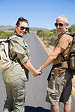 Hitch hiking couple holding hands on the road smiling at camera