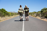 Hitch hiking couple holding hands on the road
