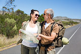 Hiking couple looking at map on the road