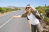 Pretty hitchhiker sticking thumb out on the road