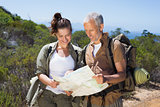 Happy hiking couple standing on mountain trail looking at map