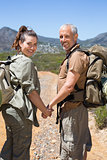Happy hiking couple standing on mountain trail holding hands