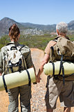 Hiking couple standing on mountain trail holding hands