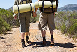 Hiking couple walking on mountain trail holding hands