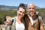 Hiking couple smiling at camera on mountain trail