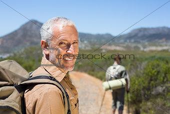 Hiking couple walking on mountain trail man smiling at camera