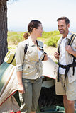 Outdoorsy couple smiling at each other outside their tent