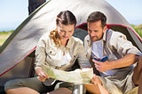 Outdoorsy couple looking at the map outside tent