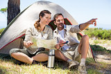 Outdoorsy couple looking at the map and pointing outside tent