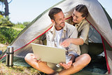 Outdoorsy couple looking at the laptop outside tent