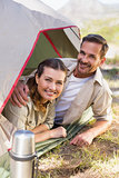 Outdoorsy couple smiling at camera from inside their tent