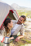 Outdoorsy couple smiling at each other inside their tent