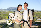 Hiking couple smiling at camera in the countryside
