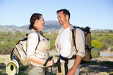 Hiking couple smiling at each other in the countryside