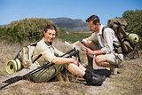 Hiking couple taking a break on country terrain