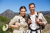Hiking couple standing and smiling at camera on country terrain