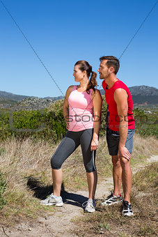 Active couple standing on country terrain