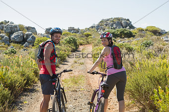 Active couple cycling in the countryside smiling at camera