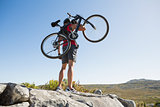Fit man carrying his bike on rocky terrain