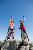 Fit cyclist couple cheering at the summit