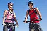 Fit cyclist couple standing at the summit smiling at camera