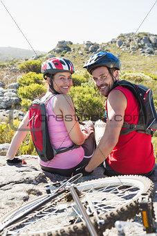 Fit cyclist couple sitting at the summit smiling at camera