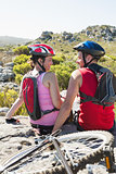 Fit cyclist couple sitting at the summit smiling at each other