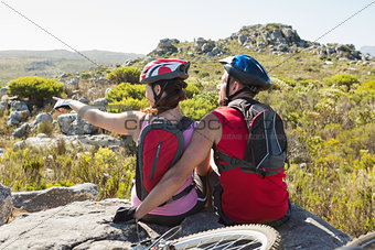 Fit cyclist couple sitting at the summit looking around