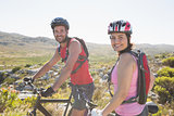 Fit cyclist couple smiling at camera on mountain trail