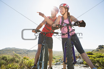 Fit cyclist couple looking around on mountain trail