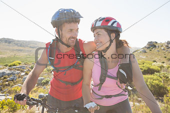 Fit cyclist couple smiling together on mountain trail
