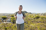 Pretty hiker smiling at camera on mountain terrain