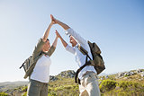 Hiking couple high fiving on mountain terrain