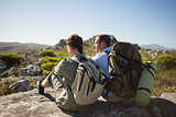Hiking couple sitting on mountain terrain