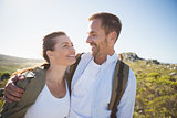 Hiking couple embracing and smiling on country terrain