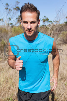 Athletic man jogging in the countryside