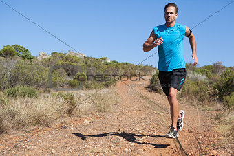 Athletic man jogging on country trail