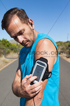 Athletic man changing the music on a run
