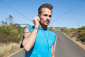Athletic man adjusting his earphones on a run