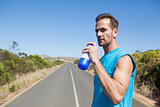 Athletic man on open road taking a drink