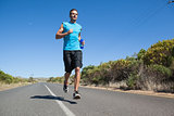 Athletic man jogging on open road holding bottle