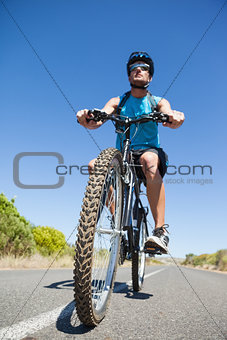 Athletic man cycling on open road